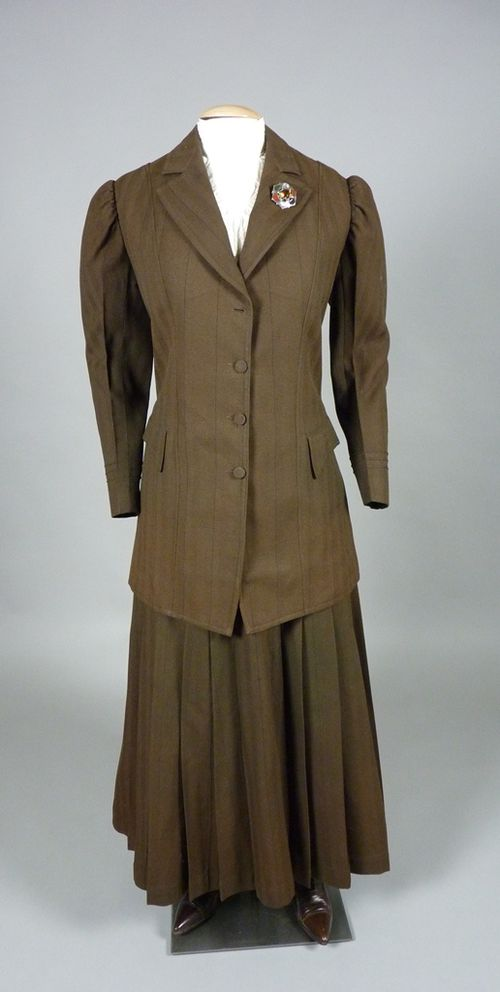 A brown tweed tailored suit of 1908, showing the beginning of a more streamlined silhouette, and with a more practical hemline slightly above the ankle, worn with an embroidered cotton dickey. Daughters of the American Revolution Museum.