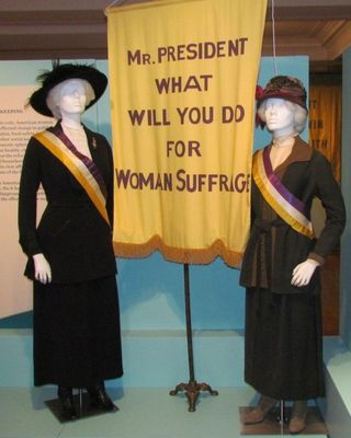 Two manikins on display at the Daughters of the American Revolution Museum represent the White House Picket Line vigil kept daily by members of the National Woman's Party (organizers of the March 1913 parade) starting in February 1917. Suits and hats, courtesy Shippensburg University Fashion Archives and Museum. Sashes and original banner pole, courtesy the Sewall-Belmont House and Museum. Reproduction banner.