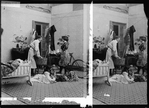 """An example of a stereograph which pokes fun at the domestic upheavals caused by the ascent of the ""New Woman."" This emancipated woman is preparing to ride her bicycle after giving instructions on laundry and child-rearing to her confused husband, wearing an apron."""