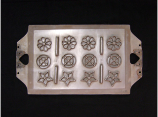 Nordic Ware used this mold to manufacture the irons for Swedish rosettes. The mold is made of heavy metal and has a flower, circle and star design repeated four times to make twelve irons at a time.