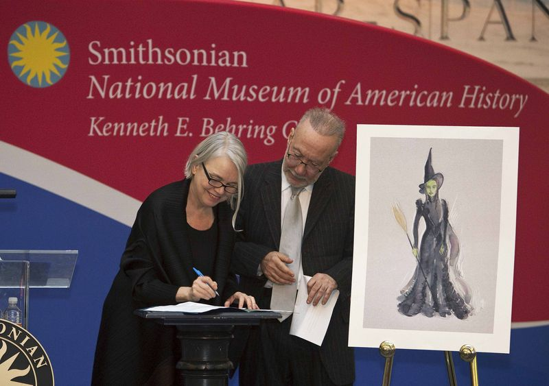 Costume designer Susan Hilferty signing the deed of gift for the Elphaba costume