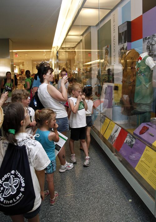 Visitors examine Girl Scout artifacts on display during Girl Scouts Rock the Mall