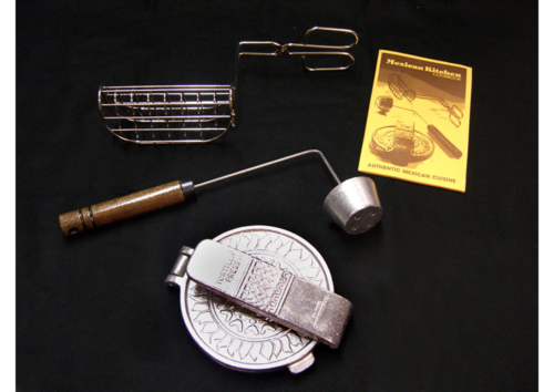 This Mexican Kitchen Cookware Set was manufactured by Nordic Ware in 1982. The set consists of three items: an aluminum tortilla press with a sun design, a taco maker including a wire basket to shape the tacos, and a cup shell former that holds down and shapes tortillas as they fry.