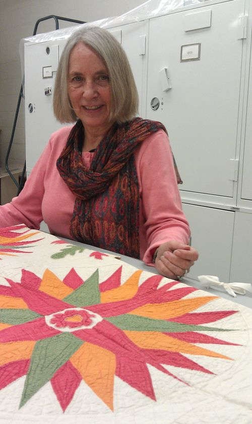 Volunteer Virginia Eisemon with one of the quilts in the National Quilt Collection