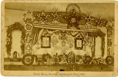 Photograph (cabinet print) of Town Hall, Bolton, Decoration Day, 1886, showing elaborate decorations, including framed pictures of uniformed soldiers, flags, G.A.R. emblems, flowers, etc.