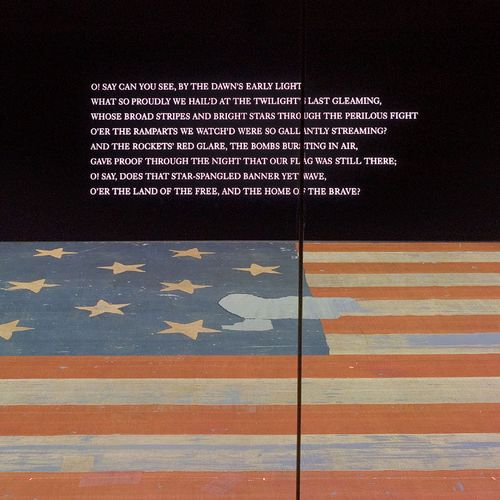 The first stanza of the national anthem is projected prominently on the wall above the Star-Spangled Banner in the museum.