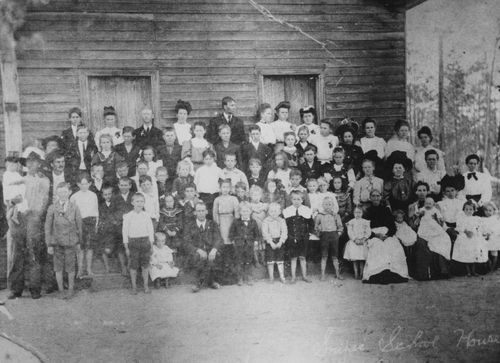 "Dr. Clough included this photograph with his story: ""My mother is the little barefoot girl standing in a dress on the right next to a woman known as Grandma Snipes—she is the older woman seated with an apron on and a dark shirt. My grandmother is the handsome young woman standing in the back row to the right of the picture flanked by a woman leaning to the right and one with a dark dress."""