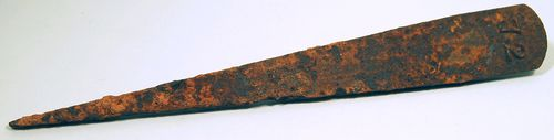 Rusted metal object in the shape of an exclamation mark: large and curved on one side, narrow in middle, and pointed at one end. Possibly this is Sarah Savage's rusted iron grave marker, #72 from Central State Hospital, Georgia