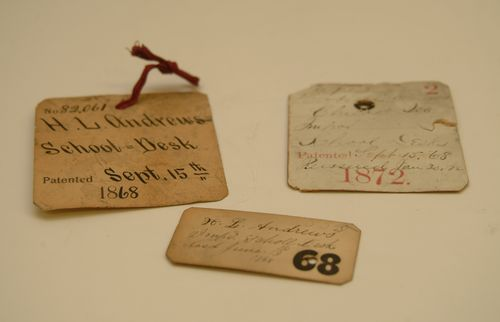 Patent tags for Herbert L. Andrew's school desk model