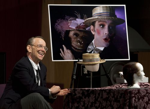 "Joel Grey with the straw hat he wore in the film, with an image from its famous scene. Although created in 1972, the straw hat is remarkably stable. ""It has a few dents in it, but it's relatively hardy,"" said curator Dwight Blocker Bowers."