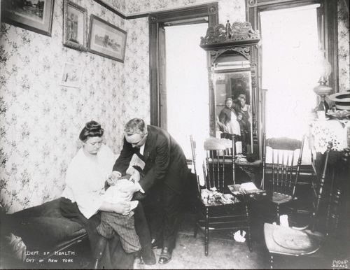 A boy receives an antitoxin injection while being held by a nurse and doctor, likely from the New York City Health Department. The photographer lined up a clever composition that allows us to see what I presume is his family's worried reaction in the mirror. I love that we can see the father wiping his brow and the sister peeking out from behind her mother's skirt.