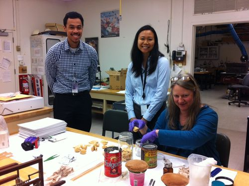 Intern Emilio Eusebio, author and Fellow Chrissy Yee Lau, and Conservator Beth Richwine wait in eager anticipation to see the contents of the can
