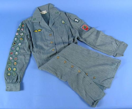 Girl Scout uniform belonging to Joan Clark c.1943-1948. This style of uniform was introduced just before WWII and originally included a zipper. Wartime rationing saw the zipper replaced with green buttons.