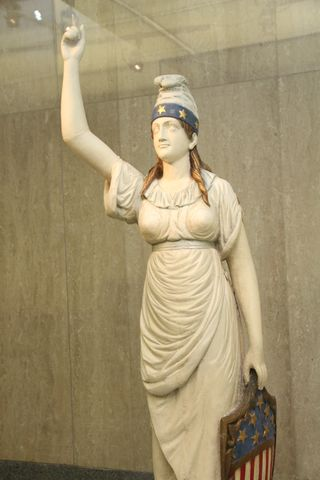 "Columbia, 1850–1880. Columbia was widely recognized as the historical female personification of the identity of the United States. Derived from the Latin for ""The lands of Columbus,"" Columbia was often associated with ships and places. By 1920, the Statue of Liberty in New York Harbor replaced Columbia as the symbol of America, welcoming waves of immigrants to new lives in a new homeland."