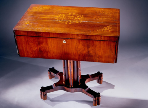 The maker of this piano is unknown, but it is thought to have been made in Germany or Austria in the 1840s. This is a small square piano contained in a work table, which has receptacles in the top of the case for sewing implements. Such multi-purpose instruments illustrate the importance of the piano to the training of women in the 19th century.