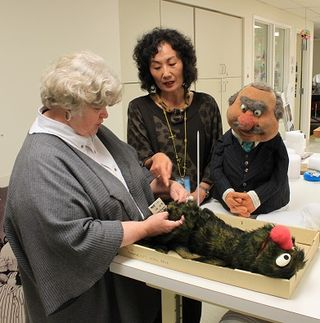 "Bonnie and Sunae discuss how to proceed with ""old Grover"" as J.P. Grosse looks on"