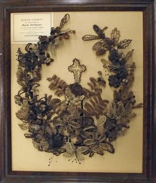 This wreath, made by Mrs. Jemima Cattell Little in Newton, Iowa, around 1865, would have been hung on a wall as decoration. The hair was wrapped, woven, or braided around gauged wire to help keep its shape.