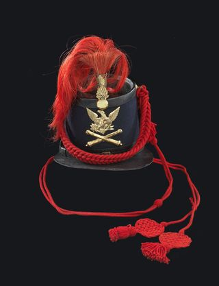 When photographing objects, it's important to get all the details right. In this retaken shot, the hat's red braid drapes over the front, where we can also see the brass pieces that made the hat so difficult to shoot.