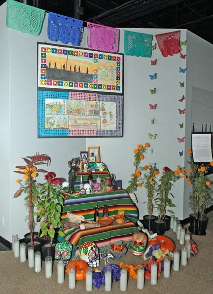 Marigolds, an important Day of the Dead symbol, flanked either side of the ofrenda, providing a colorful beacon and attractive fragrance said to draw ancestors back to earth for the annual Dia de los Muertos reunion.