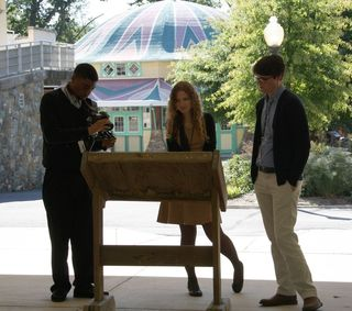 Interns Nicholas Nchamukong, Joy Lyman, and Harry Clarke read about the history of Glen Echo Park. The carousel that was the site of the protest is in the background.