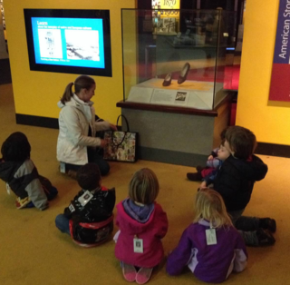 Smithsonian Early Enrichment Center students sit on the floor to explore the Ruby Slippers