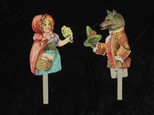These paper puppets of fairy tale characters Red Riding Hood and the Wolf are from the 1900s. They are cut-out color chromolithographs mounted on cardboard. They are manipulated by a cardboard stick extending through a slot at the bottom of the puppet.