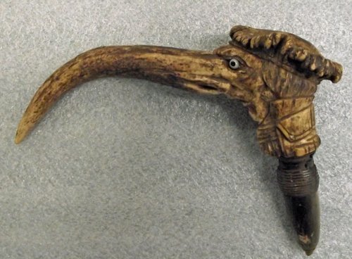 Although we don't know many specifics about this object, we do know that the museum collected it as an example of material manufacturing; the cane handle is made from elk horn. There are threads at the bottom that would allow the handle to be screwed onto a cane. When removed, another hole appeared, and the handle could become a pipe.