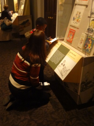 One-on-one conversation is helpful as this young reviewer evaluates one of the display cases