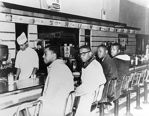 On the second day of the Greensboro sit-in (1960), Joseph A. McNeil and Franklin E. McCain are joined by William Smith and Clarence Henderson at the Woolworth lunch counter in Greensboro, North Carolina. (Courtesy of Greensboro News and Record).