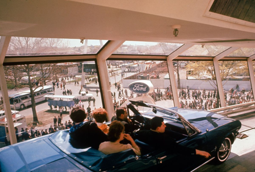 Mustang convertible on the Magic Skyway at the Ford pavilion, 1964 New York World's Fair.  The family in the car enjoyed a glassed-in view of the fairgrounds and a ride through the pavilion with its prehistoric dioramas, city of tomorrow, and Ford showroom.  Photo credit:  Getty Images.