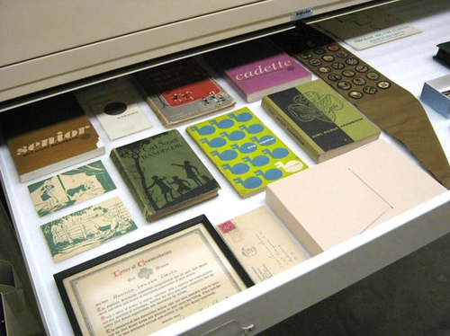 material and subject. Mainly paper objects and books are tucked into this drawer. The Girl Scout objects are comfortably situated in drawers inside large cabinets, sorted and grouped together by