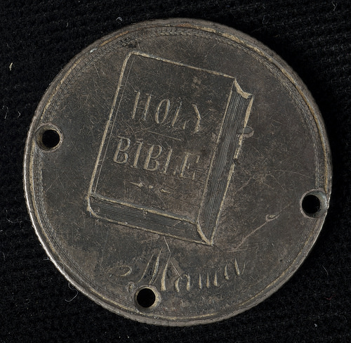 "It is reverse hand engraved book with the words ""Holy Bible."" The word ""Mama"" is underneath the book. NU*247637.0004."