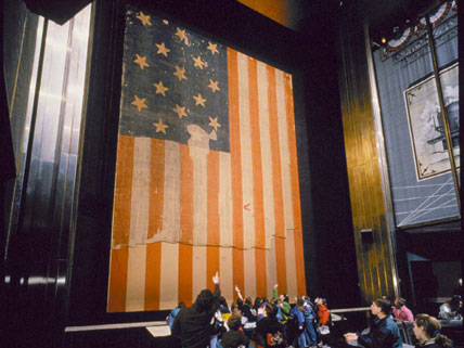 The flag hung vertically for almost 40 years. Now it's at a 10 degree angle in an hypoxic environment which protects the flag by reducing oxygen damage and suppressing fires.
