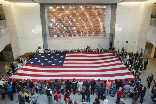 Museum visitors participate in a flag folding while singing (or humming) the anthem