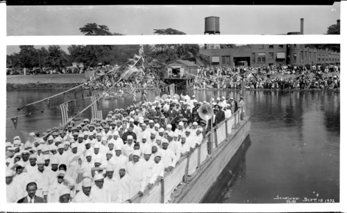 Removing one's hat before the flag, although advised by the Flag Code, depends on the circumstances. In this 1932 photograph by Addison Spurlock, church members participating in a group baptism on the Potomac River wear hats while standing under many American flags.