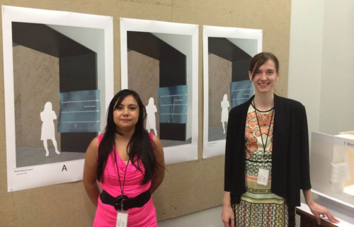 Interns Daisy Alonso (left) and Emma deVries (right) prepare to present their summer project to Director John Gray