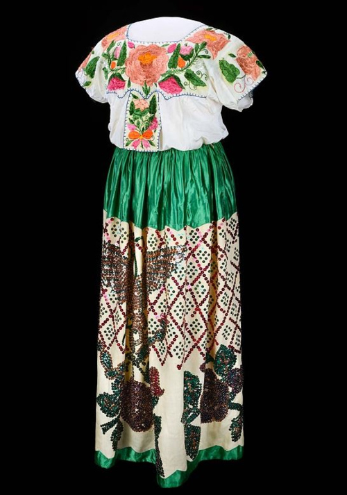 Mexican-style dress worn from around 1960. Bearing the colors and Aztec eagle design of the Mexican national flag, entertainers wore the dress during promotional events at El Chico restaurants. It is currently on display in our food history exhibition.