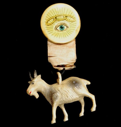 The button is made of celluloid and has an image of an eye with a three-link piece of chain above it. A toy goat dangles from the attached ribbon. The goat has the Viscoloid Co. trademark. It is white with grayish highlights. The button is unmarked. The three-link chain is the symbol of the Independent Order of Odd Fellows. NMAH-AHB2008q11193