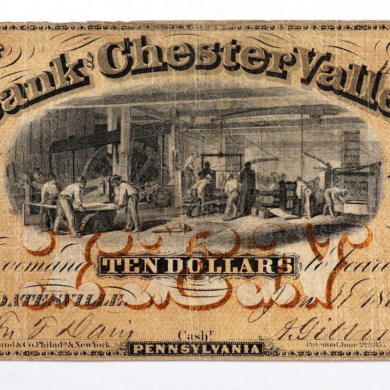 Detail of ten dollar note showing illustration of an interiror iron foundry with figures working