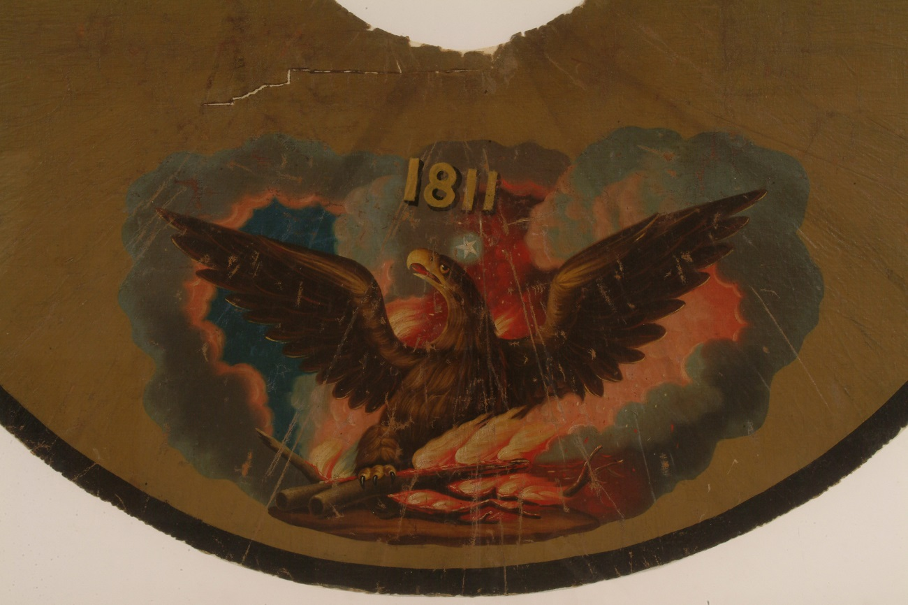 "A yellowed cape made of oilcloth. The painting in the center shows a phoenix rising from flames, with a star above his head and the words ""1811."""