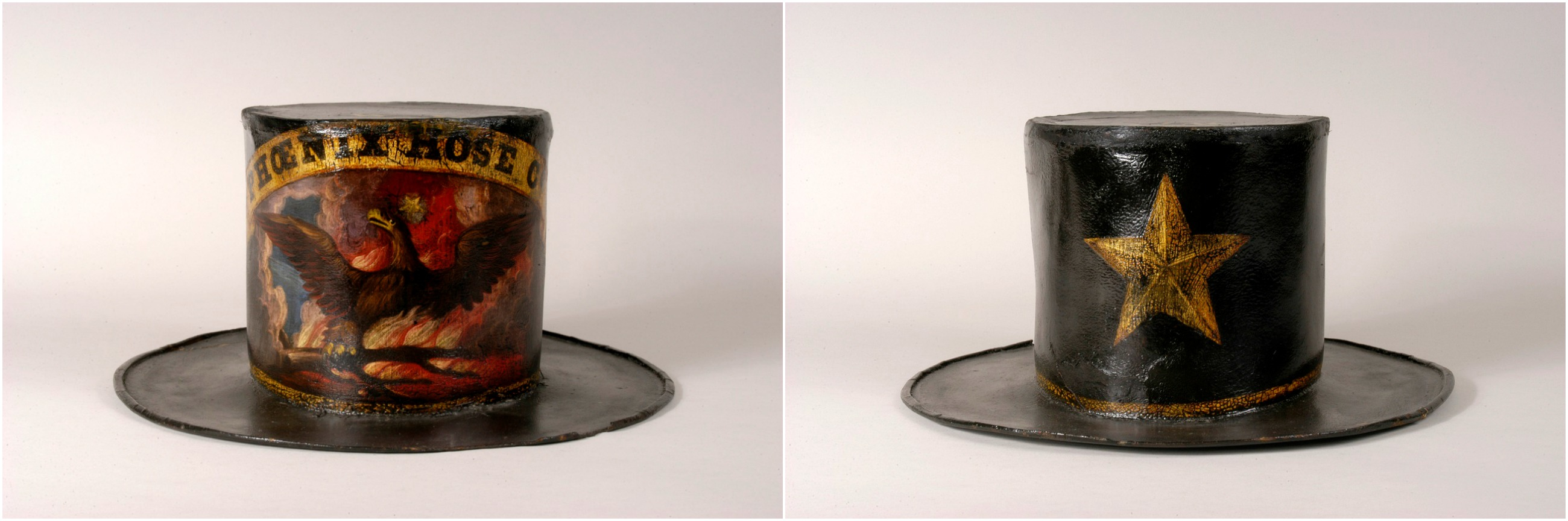 "Two hats, the shape of top hats. They're shiny--possibly the material, possibly what they were painted with. Both are dark with painted decorations, one shows a Phoenix rising from flames under the word ""Phoenix Hose Co."" The other a simple golden star."