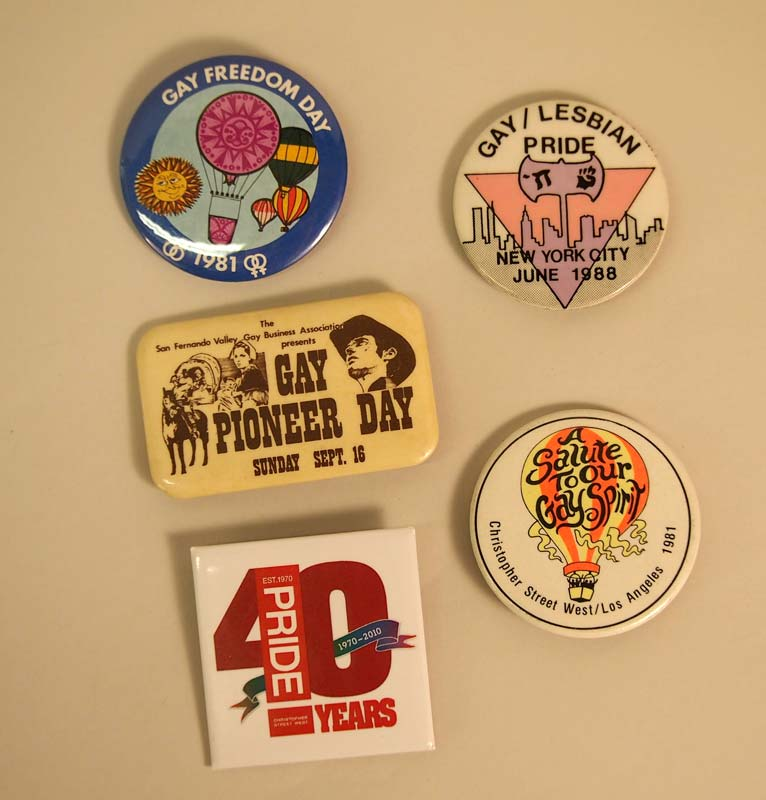 A group of buttons with slogans like 'Gay Freedom Day', 'Gay Pioneer Day', and 'Gay/Lesbian Pride, New York City June 1988'