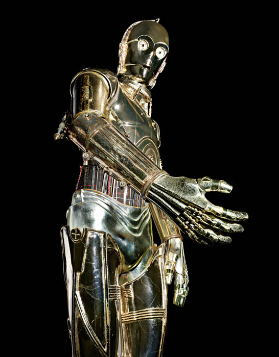 C-3PO a shiny, golden humanoid robot stands with his arm closest to the lens of the camera.