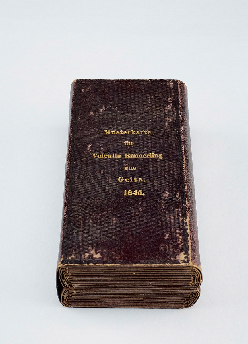 "A closed brown leather book with the words ""Musterkarte fur Valentin Emmerling au Geisa. 1845."""