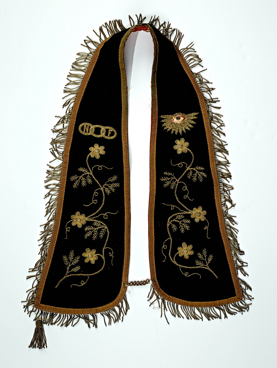 A purple fraternal collar, which would hang over the shoulders like a stole or a shaw. It is opulently decorated with golden embroidery, gold fringe, and a hand painted eye.