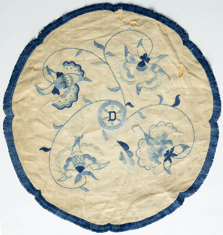 A white doily with embroidery in different shades of blue.