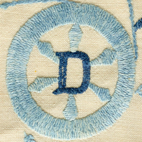 An embroidered light blue wagon wheel shape, with an embroidered dark blue capital D in the center.