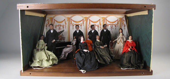 A diorama showing dolls of seven women, four men, and a piano.