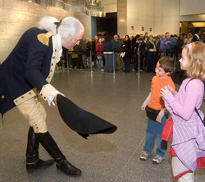 An actor portaying George Washington meets with some young Museum visitors