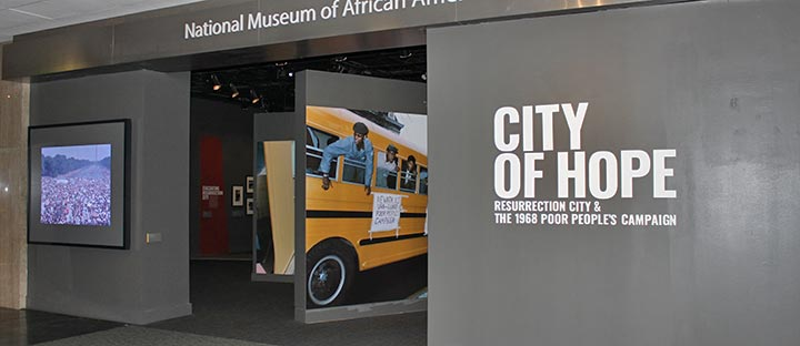 A view of the front of the City of Hope exhibition. Graphics show a bus with protesters and a video shows a crowd in Washington, D.C.